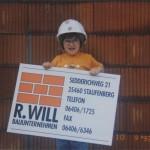 Kleines Kind mit einem Schild von Bauunternehmen Will